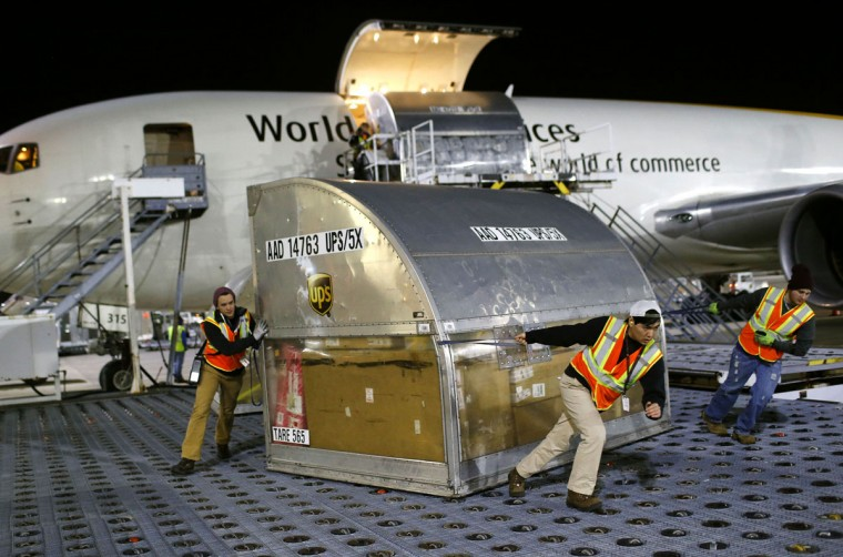 UPS workers guide a container across a floor containing casters after it was unloaded from an airplane at Worldport in Louisville, Ky. (AP Photo/Patrick Semansky)