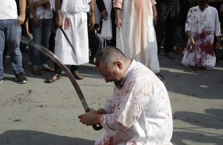 A Bahraini Shiite Muslim flagellates himself with a sword as part of the Arbaeen ritual in Muharraq, Bahrain, Thursday, Dec. 3, 2015. (AP Photo/Hasan Jamali)