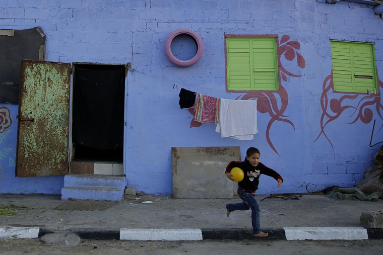 In this Saturday Dec. 19, 2015 photo, a Palestinian boy runs by a painted house in the Shati Refugee Camp in Gaza City. A group of two dozen artists has painted the walls, doorsteps and facades of all the houses along a one-mile-long (1.5 kilometer-long) edge of the camp, including in the area where Hamas chief Ismail Haniya lives.(AP Photo/Hatem Moussa)