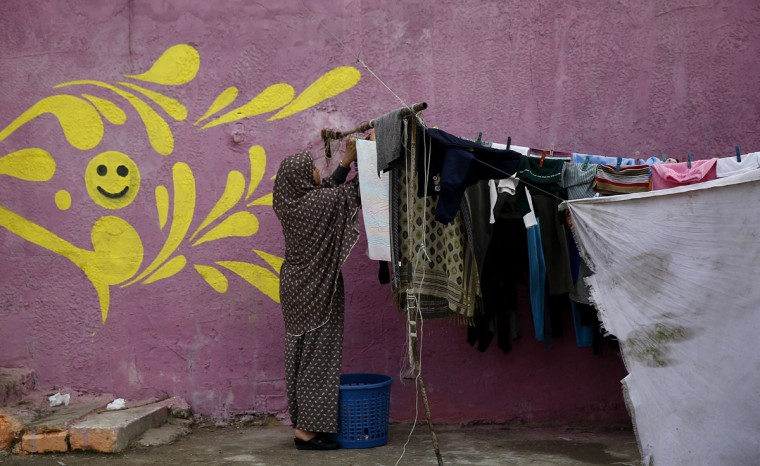 In this Saturday Dec. 19, 2015 photo, a Palestinian woman hangs laundry in front of her painted house in the Shati Refugee Camp in Gaza City. A group of Palestinian artists have just completed painting the walls, doorsteps and facades of all the houses on the one-mile-long (1.5 kilometer-long) western edge of the camp, which was a gray concrete symbol of poverty of the Gaza Strip. (AP Photo/Hatem Moussa)