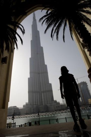 A young woman looks at the Burj Dubai, the world's tallest tower in Dubai, United Arab Emirates, Monday, July 13, 2009. (AP Photo/Kamran Jebreili)