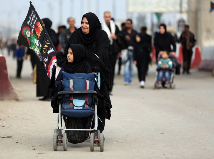 Shiite pilgrims march to Karbala for the Arbaeen ritual in Baghdad, Iraq, Tuesday, Dec. 1, 2015. (AP Photo/Hadi Mizban)