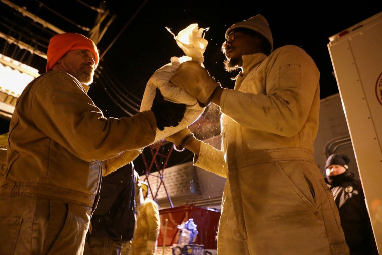 In this Tuesday, Dec. 29, 2015 photo, Michael Wilson, left, 45, and Bernard Wilson, 27, inmates at the Missouri Eastern Correctional Center, join several dozen volunteers in building sandbags to prevent the Big River from flooding a wage treatment plant that services High Ridge, House Springs and Fenton, in St. Louis. (Cristina M. Fletes/St. Louis Post-Dispatch via AP)