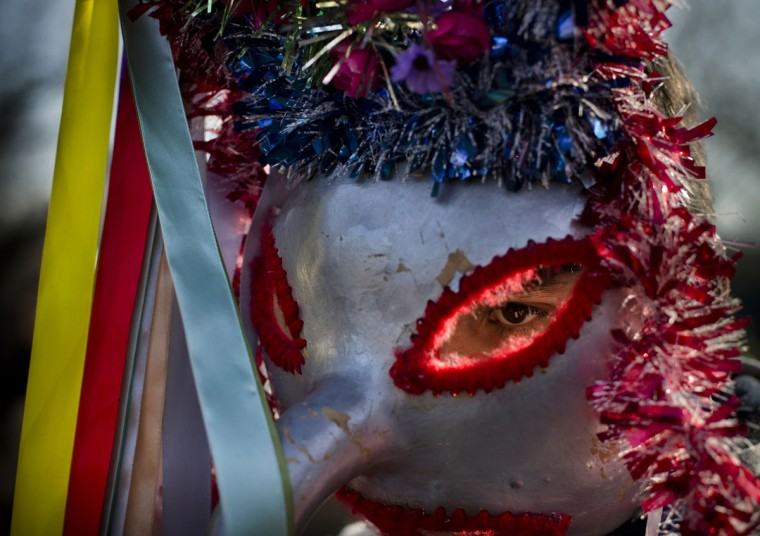 A man wearing a mask prepares to perform in a show of winter traditions at the Village Museum in Bucharest, Romania, Sunday, Dec. 13, 2015. In pre-Christian rural traditions, dancers wearing colored costumes or animal furs, toured from house to house in villages singing and dancing to ward off evil. (AP Photo/Vadim Ghirda)