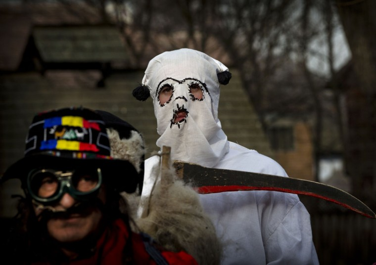 Men wearing masks prepare to perform in a show of winter traditions at the Village Museum in Bucharest, Romania, Sunday, Dec. 13, 2015. In pre-Christian rural traditions, dancers wearing colored costumes or animal furs, toured from house to house in villages singing and dancing to ward off evil. (AP Photo/Vadim Ghirda)