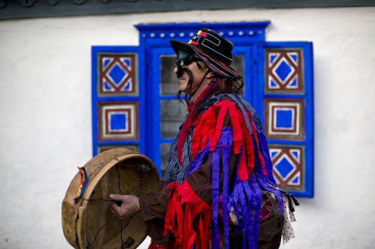 A man wearing a mask prepares to perform in a show of winter traditions at the Village Museum in Bucharest, Romania, Sunday, Dec. 13, 2015. In pre-Christian rural traditions, dancers wearing colored costumes or animal furs toured from house to house in villages, singing and dancing to ward off evil.(AP Photo/Vadim Ghirda)