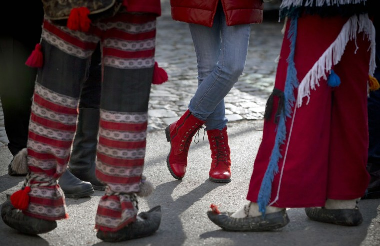 A girls sports red boots as she stands next to men wearing traditional Romanian costumes during a show of winter traditions at the Village Museum in Bucharest, Romania, Sunday, Dec. 13, 2015. (AP Photo/Vadim Ghirda)