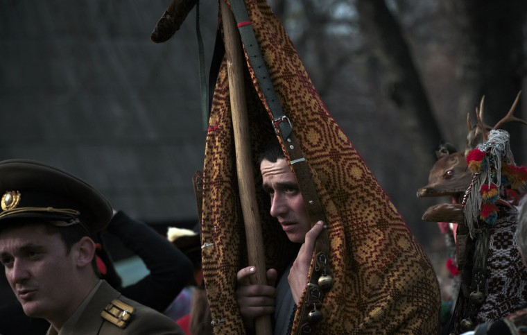 Men wearing traditional Romanian costumes along with communist-era military uniforms and animal furs prepare to perform in a show of winter traditions at the Village Museum in Bucharest, Romania, Sunday, Dec. 13, 2015. (AP Photo/Vadim Ghirda)