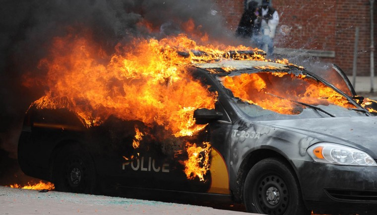 An officer vehicle burns Monday, April 27, 2015, during unrest following the funeral of Freddie Gray in Baltimore. Rioters plunged part of Baltimore, torching a pharmacy, setting police cars ablaze and throwing bricks at officers. (Jerry Jackson/The Baltimore Sun)