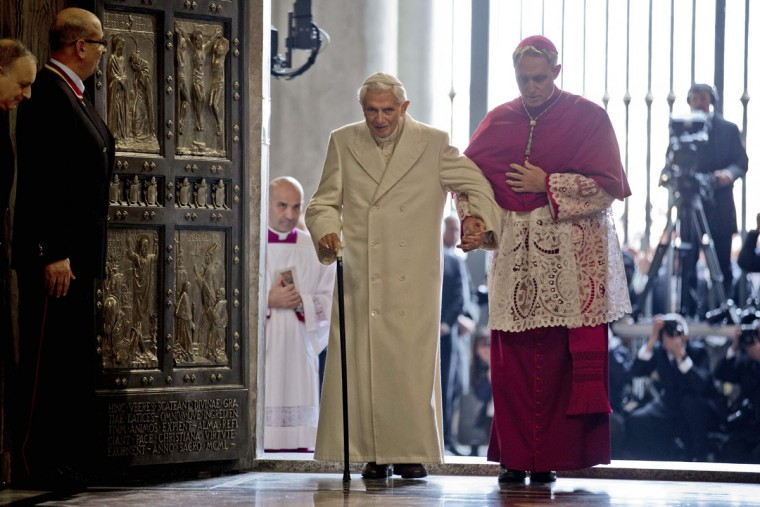 Pope Emeritus Benedict XVI enters St. Peter's Basilica accompanied by Monsignor Georg Gaenswein, right, at the Vatican, Tuesday, Dec. 8, 2015. Pope Francis pushed open the great bronze doors of St. Peter's Basilica on Tuesday to launch his Holy Year of Mercy, declaring that mercy trumps moralizing in his Catholic Church. (AP Photo/Andrew Medichini)