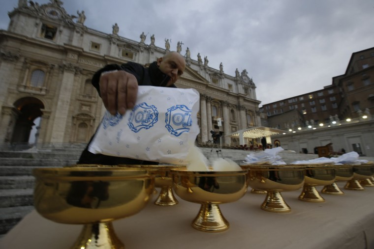 A Vatican employee pours hosts into a chalice which will be given to faithful during the communion in St. Peter's Square on the occasion of a Mass celebrated by Pope Francis for the opening of the Holy Door of St. Peter's Basilica, which formally starts the Jubilee of Mercy, at the Vatican, Tuesday, Dec. 8, 2015. (AP Photo/Gregorio Borgia)