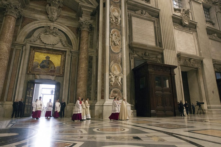 Pope Francis leads other prelates as he walks inside St. Peter's Basilica at the Vatican, Tuesday, Dec. 8, 2015. Pope Francis pushed open the great bronze doors of St. Peter's Basilica on Tuesday to launch his Holy Year of Mercy, declaring that mercy trumps moralizing in his Catholic Church. (AP Photo/Andrew Medichini)