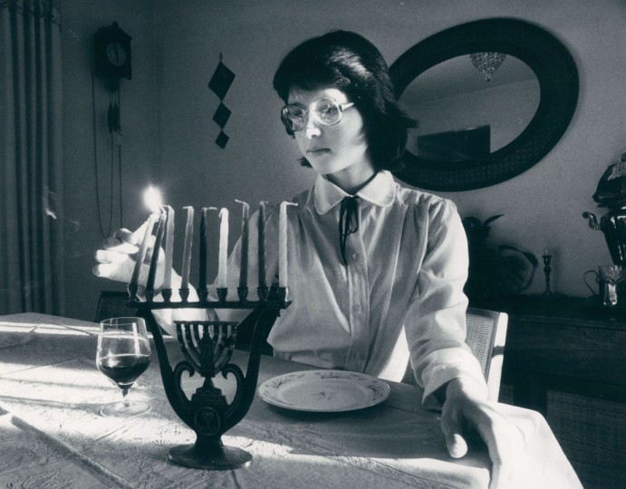 Ann Tsitlik, 12, lights a menorah. (Irving H. Phillips, Jr./Baltimore Sun, 1982)