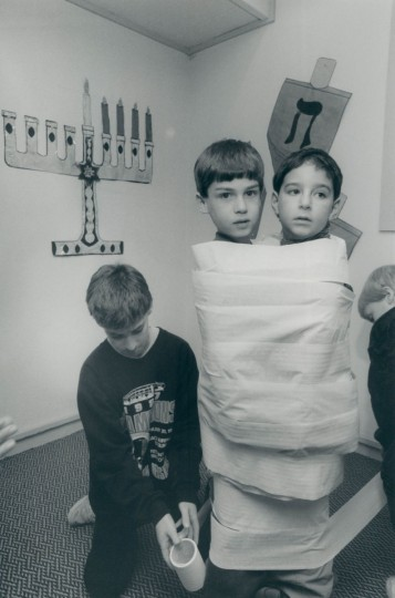 During a Hanukkah party for kids, Matthew Pagano and Adam Schulman are wrapped up like mummies by Brian Schulman and Jason Hickey. (Kim Hairston/Baltimore Sun, 1989)