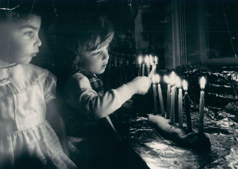 Twins Tzeona (left) and Meechael Ben-Natan, 2, help light Hanukkah candles in menorahs in family's living room window. (Irving H. Phillips, Jr/Baltimore Sun, 1979)