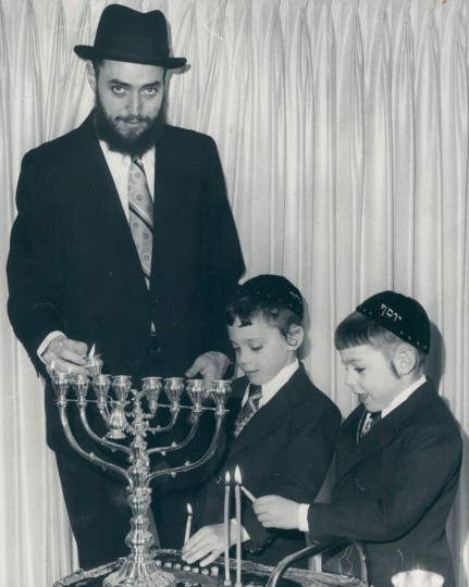 Rabbi Sheftel Neuberger and his twin sons, Boruch and Yosef, light the second candle on their Hanukkah menoras at their Pikesville home. (Carl D. Harris/Baltimore Sun, 1976)