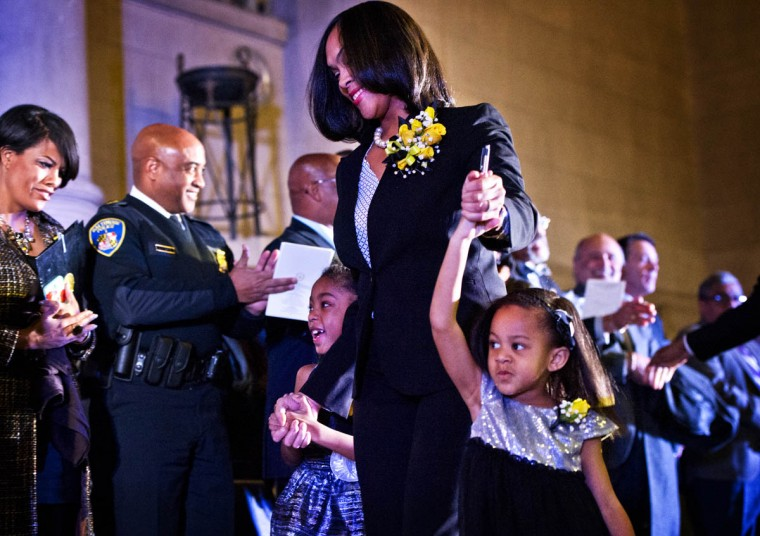 Marilyn Mosby leads her children, Nylyn, 6 (left,) and Aniyah, 4 onto the grandstand past Mayor Stephanie Rawlings-Blake and Baltimore Police Commissioner Anthony Batts. This is the inauguration of Marilyn J. Mosby as State's Attorney for Baltimore at the War Memorial in Baltimore. (Christopher T. Assaf, Baltimore Sun)