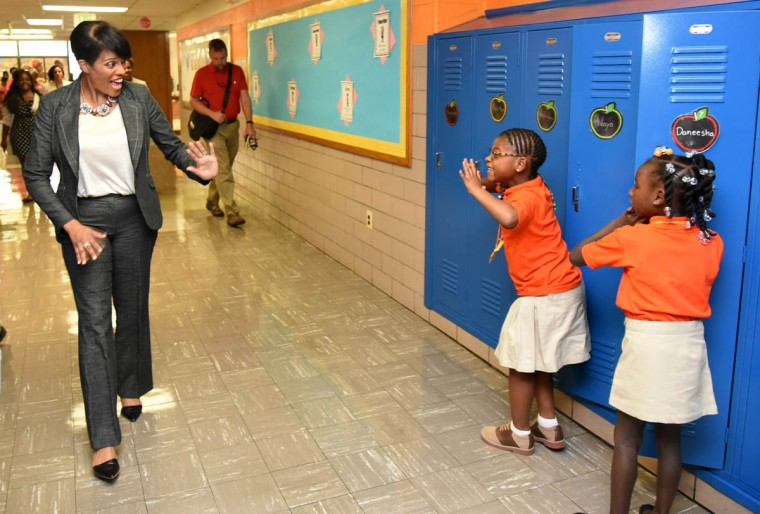 Mayor Stephanie Rawlings Blake gets an excited wave from first grader Naya Clark, second from right, who was at her locker with another first grader, Daneesha Dickerson, right, during the mayor's tour of Gilmor Elementary School on the first day of school. (Amy Davis, Baltimore Sun)