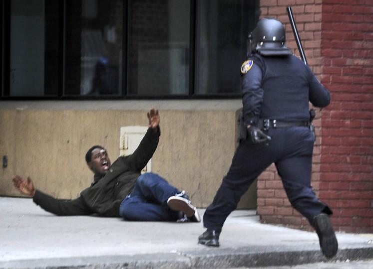 A Baltimore police man approaches a man near Lexington Market before arresting him. (Christopher T. Assaf, Baltimore Sun)
