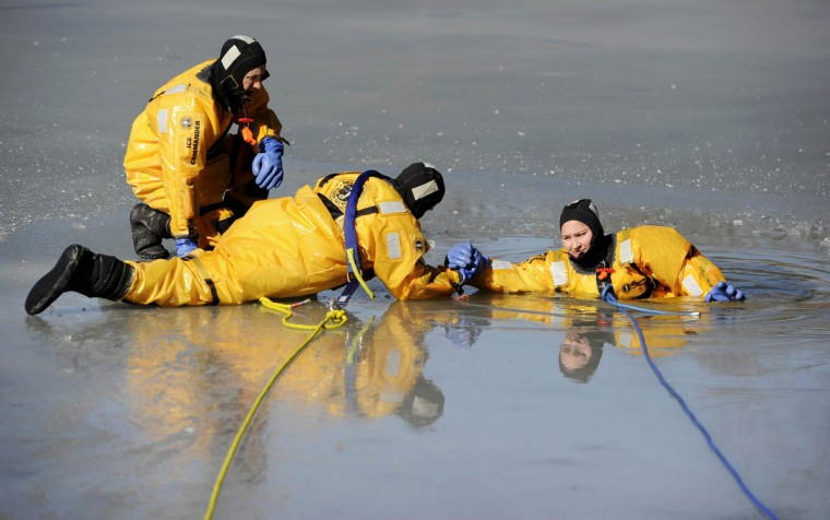 """Steve Colburn, Howard County firefighter, paramedic, reaches for """"victim"""" and fellow firefighter Ashley Bayse, as they drill under the watch of Capt. Michael Sharpe. The members of Howard County Fire and Rescue Services Station 7 performed ice rescue training drills on the frozen lake at Centennial Park in Clarksville. (Christopher T. Assaf, Baltimore Sun)"""