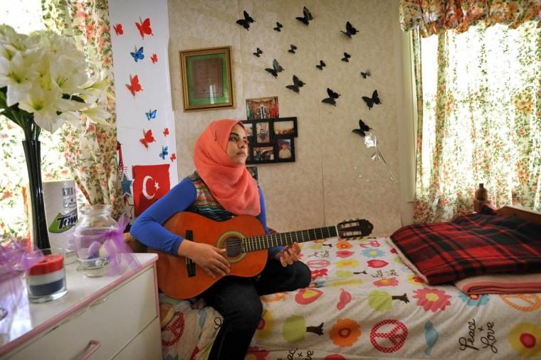 Narmin Al Eethawi, 19, playing guitar in her bedroom. (Amy Davis, Baltimore Sun)