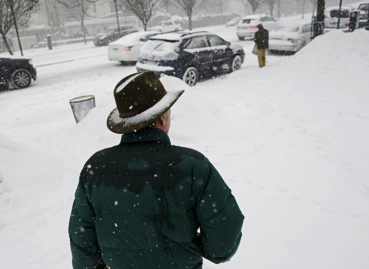 Snow collects on a pedestrian's hat as he walks along Roland Avenue in Baltimore during the snow. (Christopher T. Assaf, Baltimore Sun)