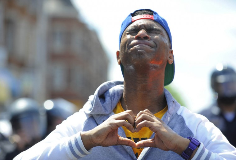 Devante Hill of Baltimore makes a heart with his hands after he was hit with pepper spray after someone threw a bottle at police. Protesters gather at the intersection of Pennsylvania Avenue and North Avenue today a day after riots broke out in Baltimore over the death of Freddie Gray. (Lloyd Fox/Baltimore Sun)