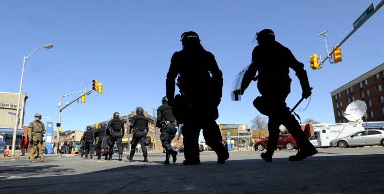 Police during a shift change as they walk across Pennsylvania Avenue shortly before most of the officers were removed from the area. This is Baltimore just days after the riots and looting that took place. W. North Avenue and Pennsylvania Avenue as the police presence begins to diminish. (Lloyd Fox/Baltimore Sun)