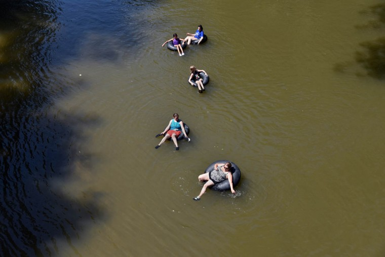 """Top to bottom, Emma Williams, 17, Dundalk, Carmen Tidwell, 11, Hamilton, Sophi Schweigman, 11, Dundalk, Melissa Tidwell, Hamilton, and Allison Schweigman, Dundalk, tube on the Gunpowder Falls on a hot Monday afternoon. Allison says """"No matter how hot it is, the water's always cold."""" (Kim Hairston/Baltimore Sun)"""
