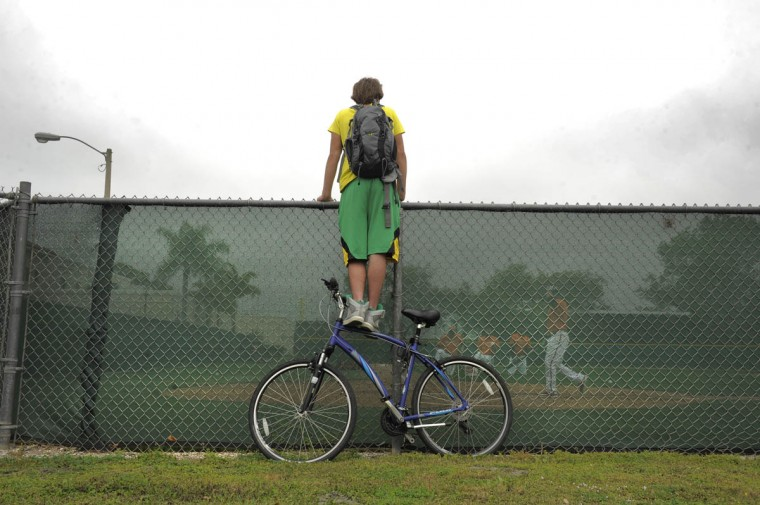 Mel Fisher, 17, vacationing from Lancaster, PA stands atop his bike to look over the fence of Earl Weaver Little Field, watching Baltimore Orioles players participate in bunting drills during spring training at the Orioles' training facility. (Karl Merton Ferron / Baltimore Sun)