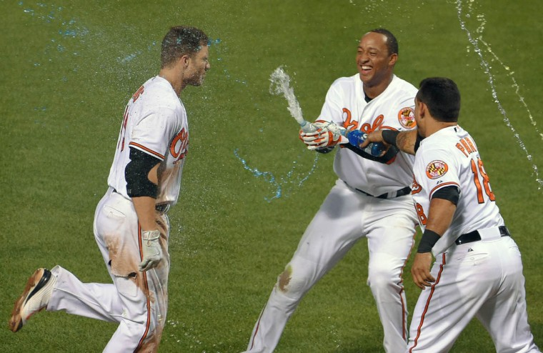 Baltimore Orioles teammates celebrate as batter Chris Davis crosses home plate after clouting a solo home run against the Tampa Bay Rays in the eleventh inning at Oriole Park at Camden Yards. Baltimore clawed back to beat Tampa Bay, 7-6, in 11 innings. (Karl Merton Ferron/Baltimore Sun)