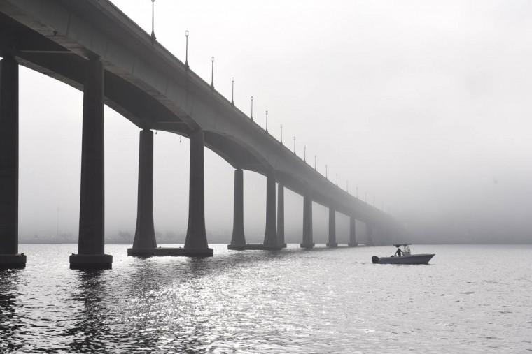 A fisherman passes under a fog-shrouded Naval Academy Bridge. ( Jerry Jackson/ Baltimore Sun)