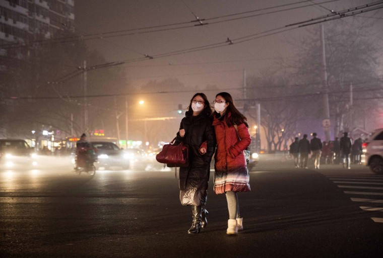 Chinese women wear masks as protection from the pollution as they cross a road on December 1, 2015 in Beijing, China. (Photo by Kevin Frayer/Getty Images)