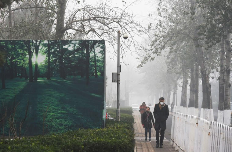 Pedestrians walk past a billboard scene of green trees and grass on a heavily polluted day in Beijing on December 1, 2015. (GREG BAKER/AFP/Getty Images)