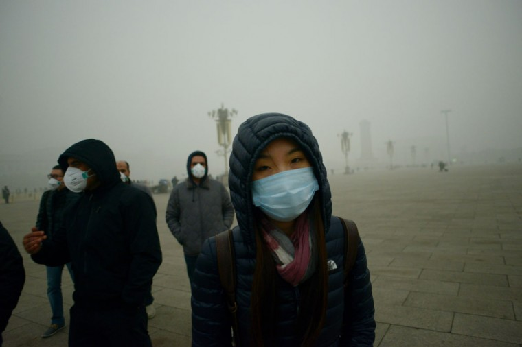 Visitors wear masks as they walk in Tiananmen Square during heavy pollution in Beijing on December 1, 2015. (WANG ZHAO/AFP/Getty Images)