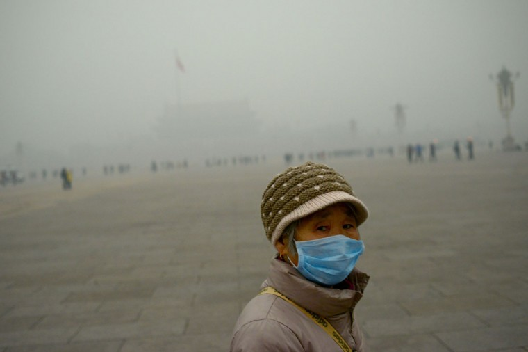 An elderly woman wearing a mask looks on as she visits Tiananmen Square during heavy pollution in Beijing on December 1, 2015. (WANG ZHAO/AFP/Getty Images)