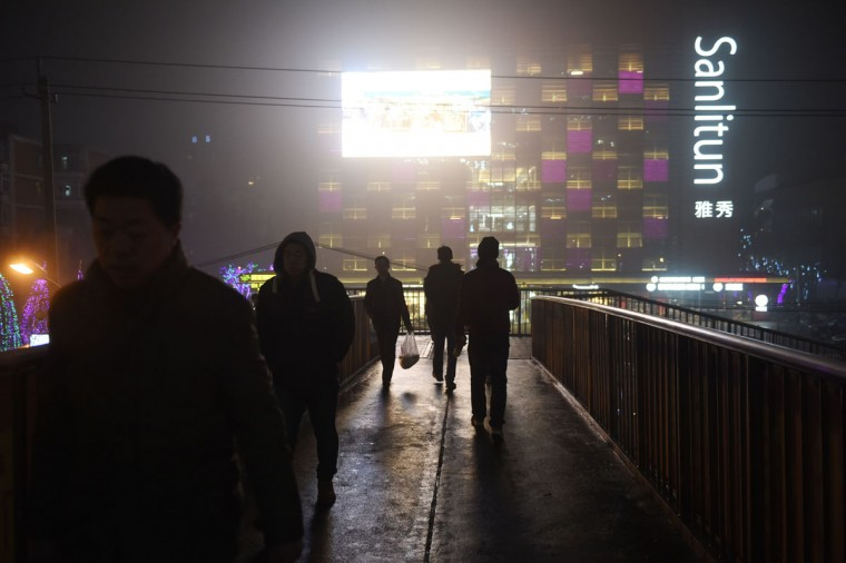 Haze is lit up by a video screen on a heavily polluted evening in Beijing on December 1, 2015. (GREG BAKER/AFP/Getty Images)