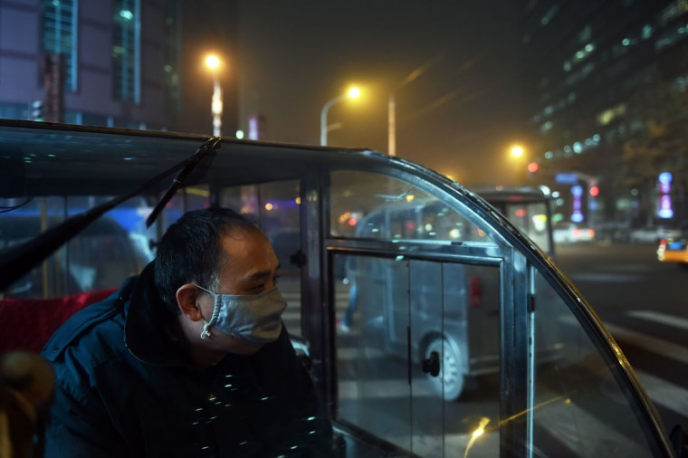 A tricycle taxi rider waits for customers on a heavily polluted evening in Beijing on December 1, 2015. Beijing ordered hundreds of factories to shut and allowed children to skip school as choking smog reached over 25 times safe levels on December 1, casting a cloud over China's participation in Paris climate talks. (GREG BAKER/AFP/Getty Images)