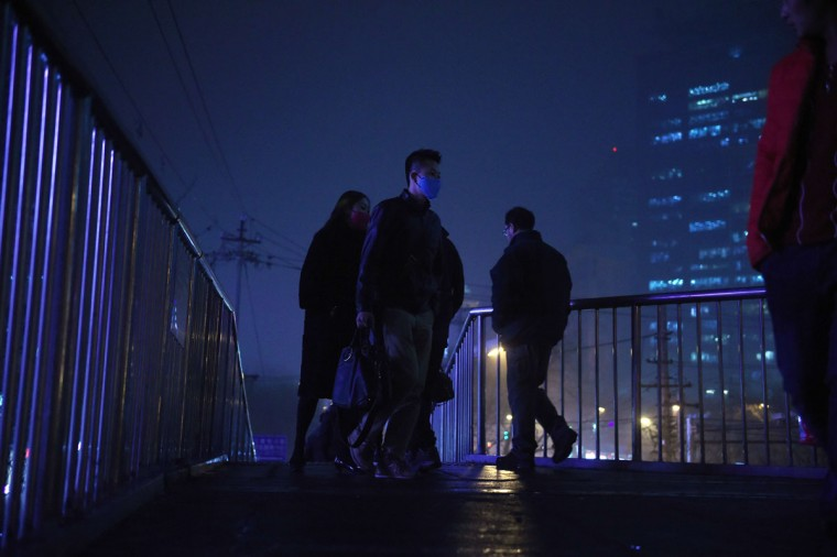 People cross a pedestrian overpass on a heavily polluted evening in Beijing on December 1, 2015. (GREG BAKER/AFP/Getty Images)
