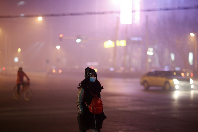 A woman wearing a mask on a polluted evening on November 30, 2015 in Beijing, China. (Photo by Lintao Zhang/Getty Images)