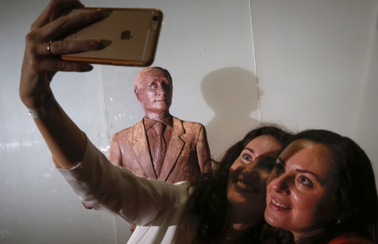 Visitors take a selfie with a chocolate statue of Russian President Vladimir Putin during the Chocolate Festival in St.Petersburg, Russia, Saturday, Dec. 5, 2015. The life-sized chocolate sculpture was created by Russian sculptor Nikita Gusev. (AP Photo/Dmitry Lovetsky)