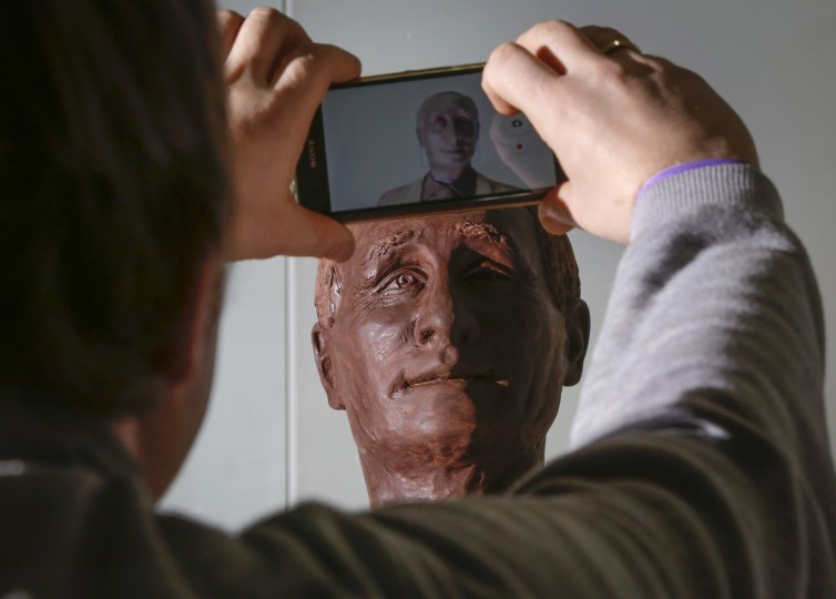 A visitor poses takes a photo of a chocolate statue of Russian President Vladimir Putin during the Chocolate Festival in St.Petersburg, Russia, Saturday, Dec. 5, 2015. The life-sized chocolate sculpture was created by Russian sculptor Nikita Gusev. (AP Photo/Dmitry Lovetsky)