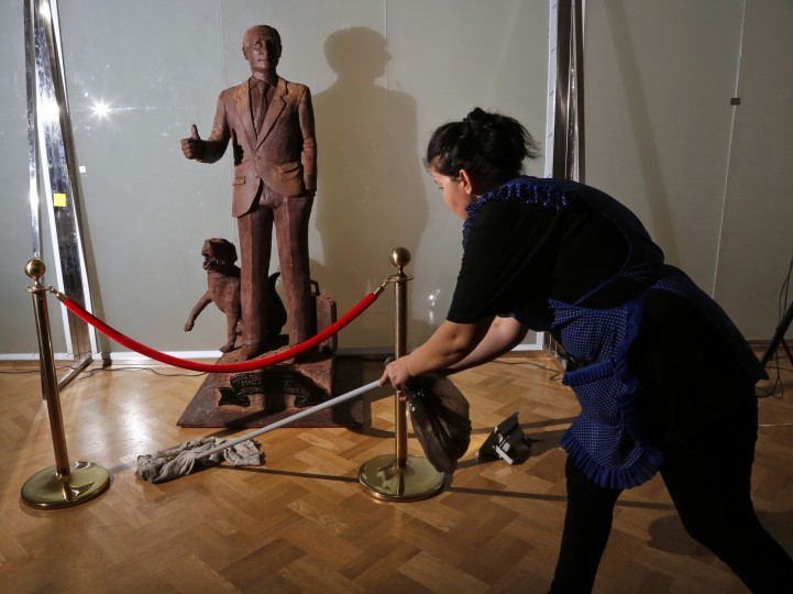 A worker cleans the floor next to a chocolate statue of Russian President Vladimir Putin during the Chocolate Festival in St.Petersburg, Russia, Saturday, Dec. 5, 2015. The life-sized chocolate sculpture was created by Russian sculptor Nikita Gusev. (AP Photo/Dmitry Lovetsky)