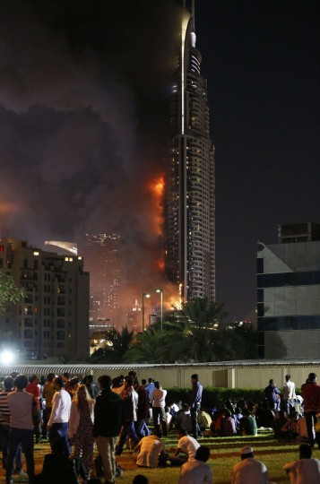 A picture taken on December 31, 2015 shows people watching the Address Downtown hotel burning after huge fire ripped through the luxury hotel near the world's tallest tower, in Dubai. People were gathering to watch New Year's Eve celebrations when the hotel caught on fire without causing casualties, according to authorities. (KARIM SAHIB/AFP/Getty Images)