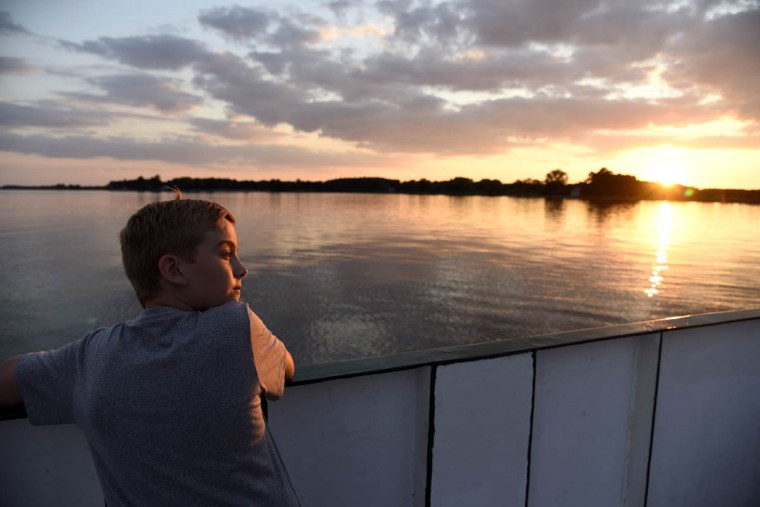 Nicholas Rados, 10 of Oxford, stands on the deck at sunset as the ferry makes its last trip of the day from the Bellevue side to Oxford. The Oxford Bellevue ferry, which crosses the Tred Avon river between the eastern shore towns of Oxford and Bellevue, is the oldest privately owned ferry in the U.S. It is owned by Captains Judy and Tom Bixler. (Barbara Haddock Taylor, Baltimore Sun)