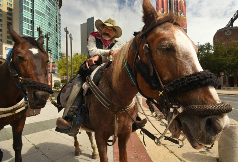 Doc Mishler, a Christian cowboy, arrived in downtown Baltimore by horseback, with a second horse at his side, to spread the word about the global crisis of hungry children. His journey began in Choteau, Montana, and his stopover in Baltimore followed a visit to Washington, DC. He stopped near Camden Yards, and asked if he was downtown. Then he asked where he could find some whiskey. (Amy Davis, Baltimore Sun)