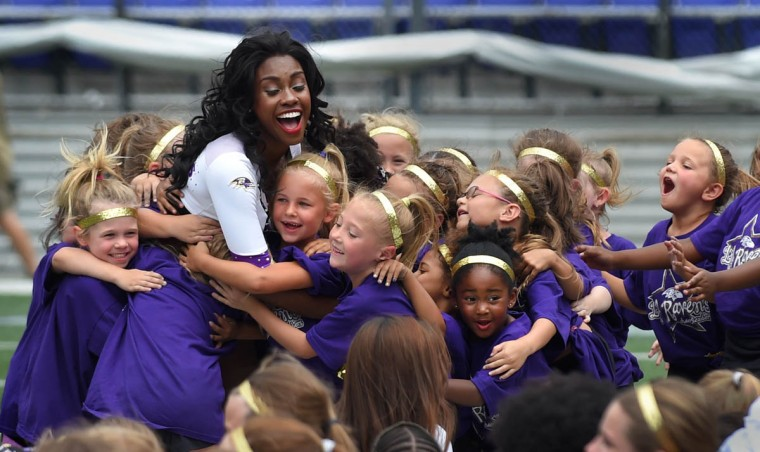 Ravens' cheerleader, Kat is mobbed by her campers after she was named cheerleading counselor of the day. The Baltimore Ravens organization is holding the Lil Ravens Cheerleading Camp for children ages 6-14 at M&T Bank Stadium. This is an all-day camp for girls and boys to learn about cheerleading and teamwork from retired and current Ravens Cheerleaders. (Lloyd Fox/Baltimore Sun)