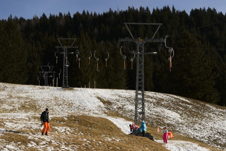 This file photo taken on December 12, 2015 shows a man walking on a snowless ski slope in the Swiss Alps resort of Davos. (FABRICE COFFRINI/AFP/Getty Images)