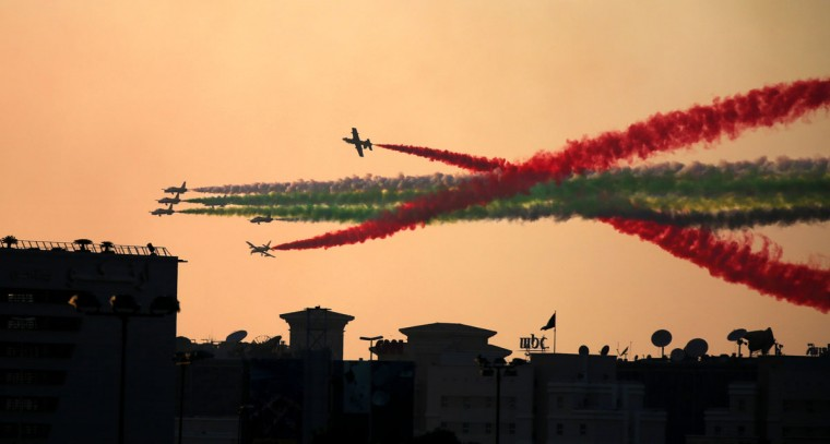 The Al Fursan aerobatic team flies over Dubai Media City on Thursday, Dec. 3, 2015, as part of the World Air Games in Dubai, United Arab Emirates. (AP Photo/Jon Gambrell)