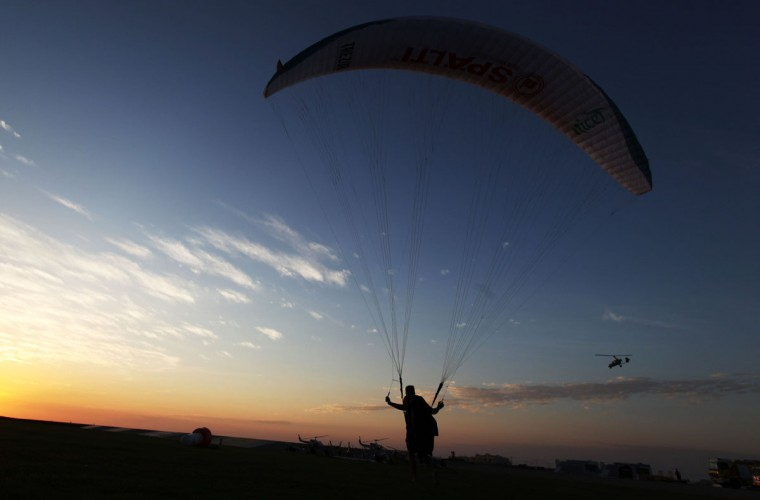 A paraguilder watches a gyrocopter fly at sunset at the World Air Games in Dubai, United Arab Emirates, on Sunday, Dec. 6, 2015. The World Air Games includes precision aerobatics, skydiving and hot air balloon competitions. (AP Photo/Jon Gambrell)